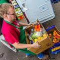 Ein Beschäftigter lädt frisch gelieferte Lebensmittel aus